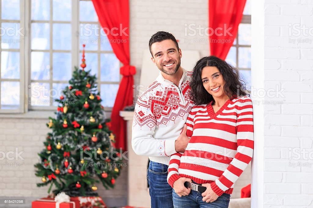 Smiling couple having fun at home for christmastide stock photo