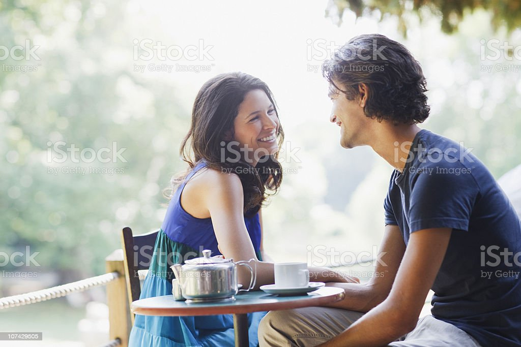 Smiling couple having tea outdoors stock photo