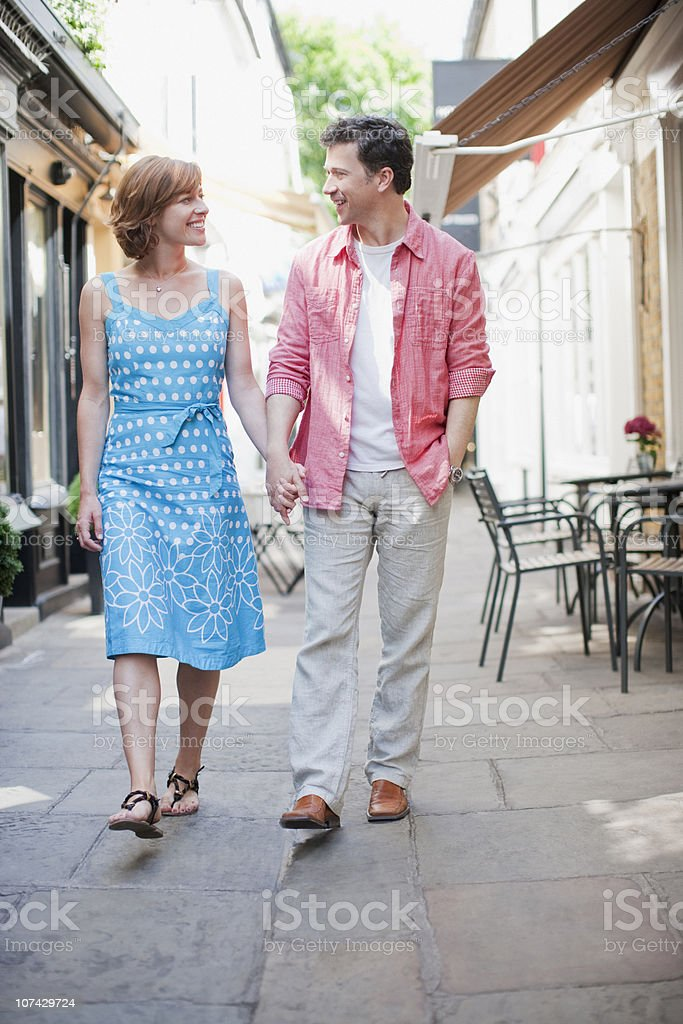 Smiling couple holding hands and walking in town royalty-free stock photo
