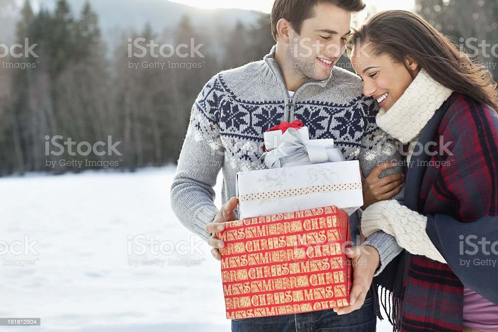 Smiling couple hugging and holding Christmas gifts in snow royalty-free stock photo