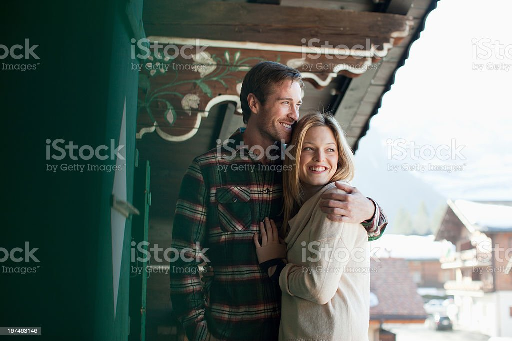 Smiling couple hugging on cabin porch stock photo