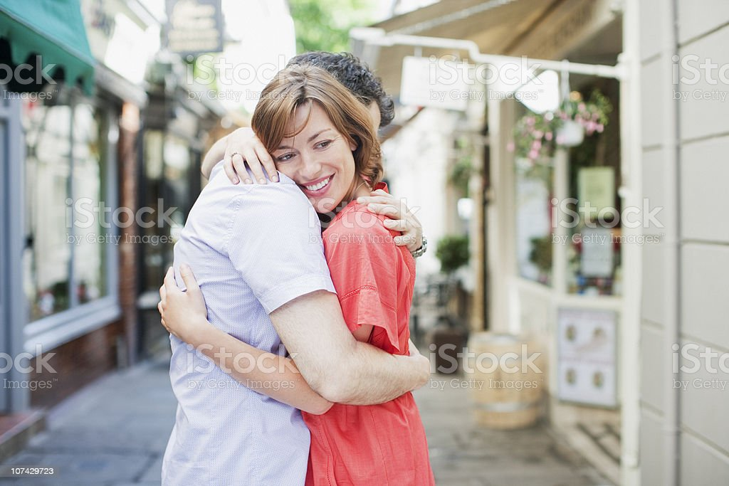 Smiling couple hugging outdoors in town royalty-free stock photo