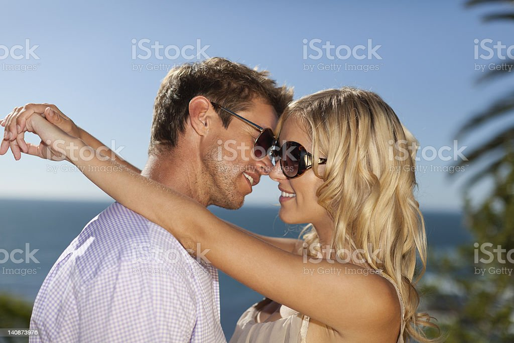 Smiling couple hugging outdoors stock photo