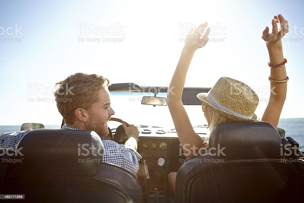 Smiling couple in a convertible on a sunny day stock photo