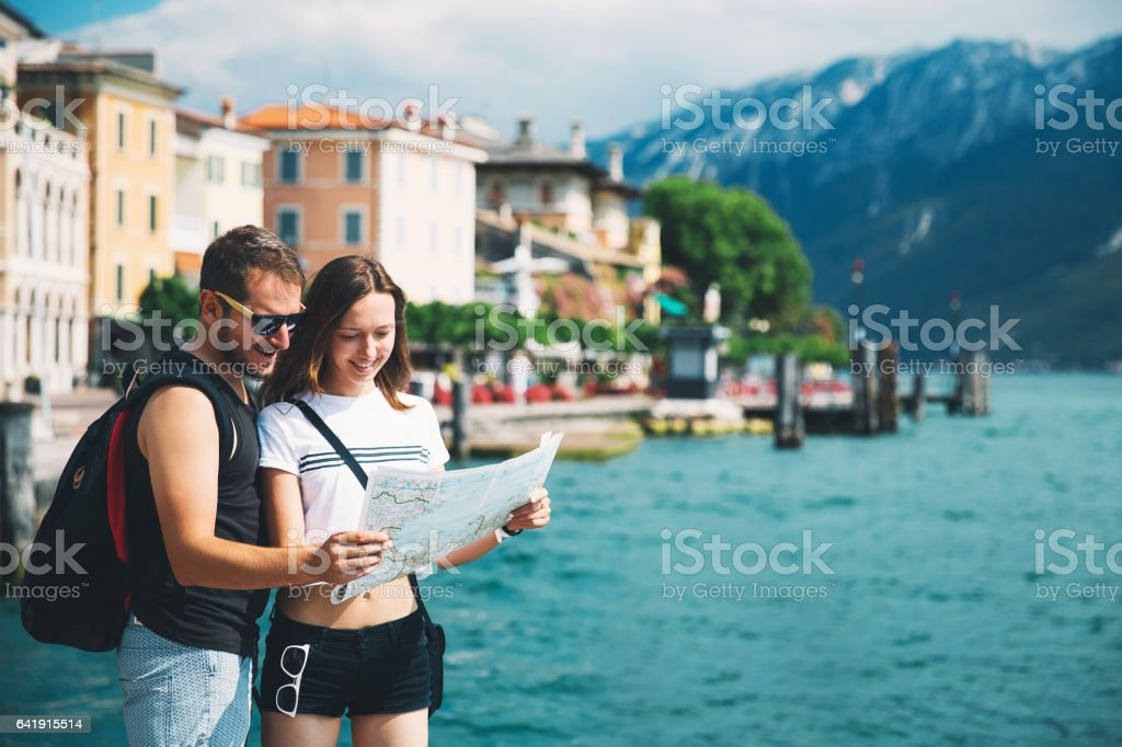 Smiling couple in love with a map at Lake Garda stock photo