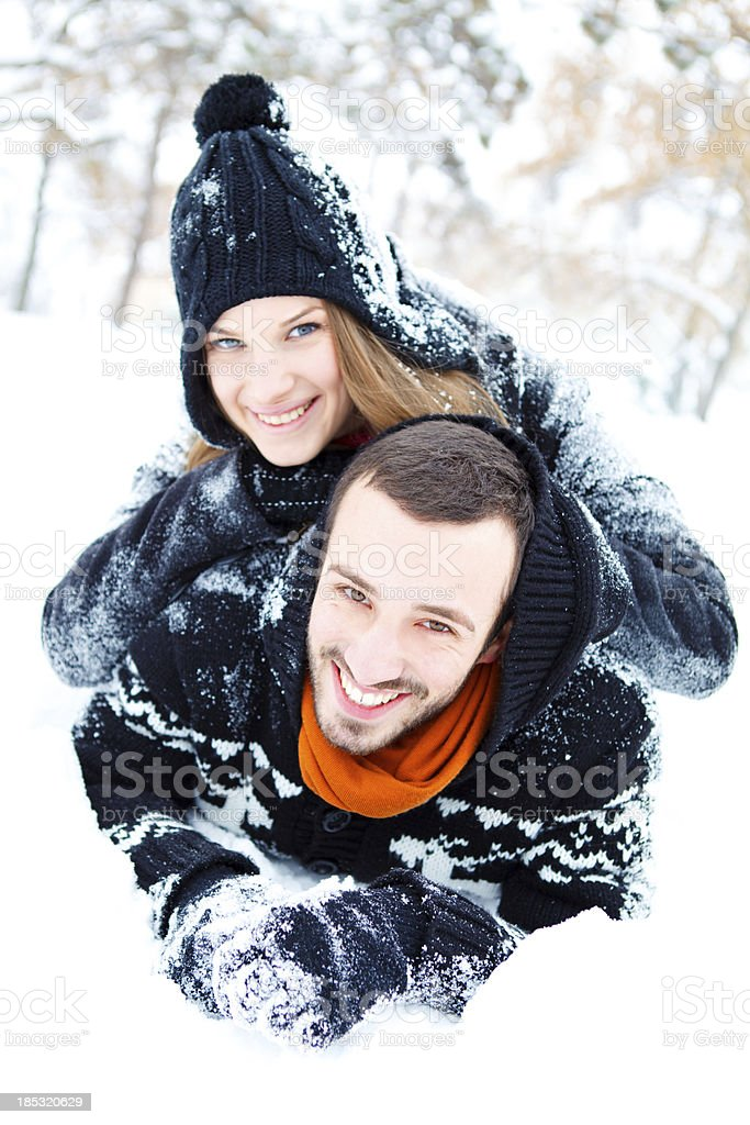 Smiling couple laying in snow royalty-free stock photo
