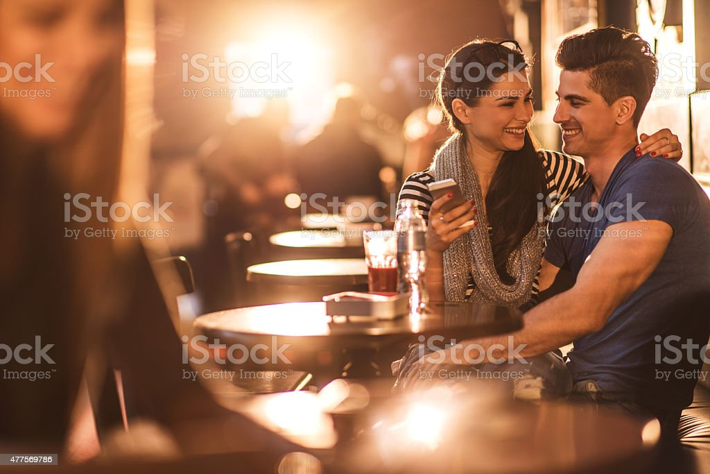 Smiling couple looking at each other and using cell phone. stock photo
