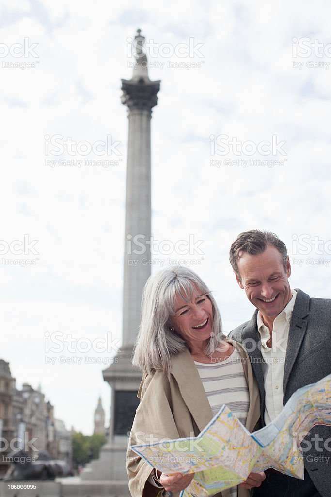 Smiling couple looking at map under monument royalty-free stock photo
