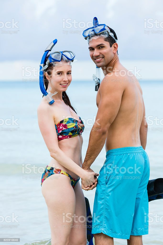 Smiling couple looking behind wearing scuba gear mid waters stock photo
