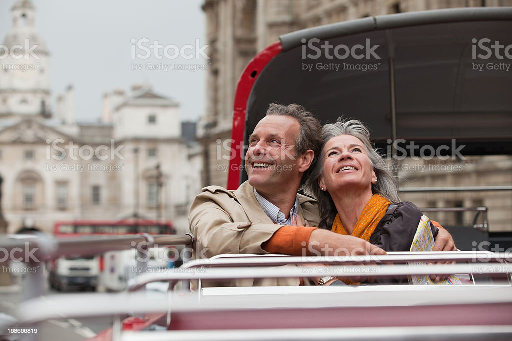 Smiling couple looking up on double decker bus in London stock photo