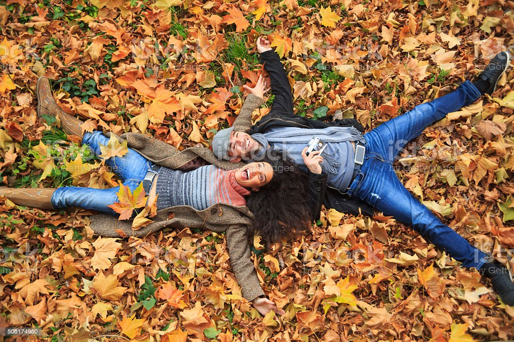 Smiling couple lying down on leaves carpet stock photo