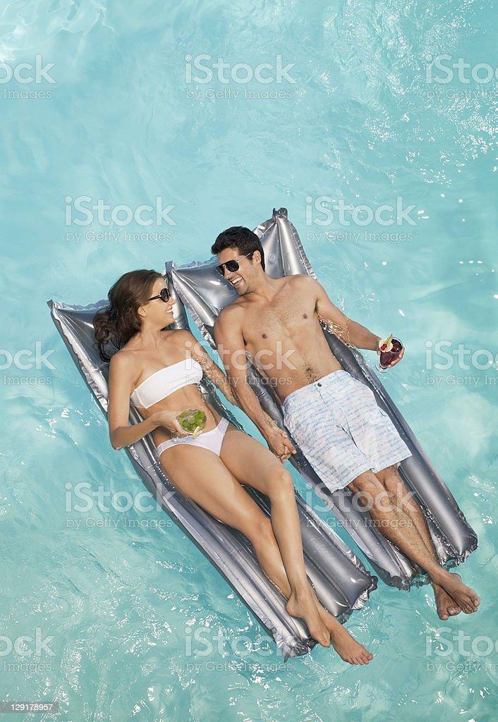 Smiling couple lying on raft while holding glass stock photo