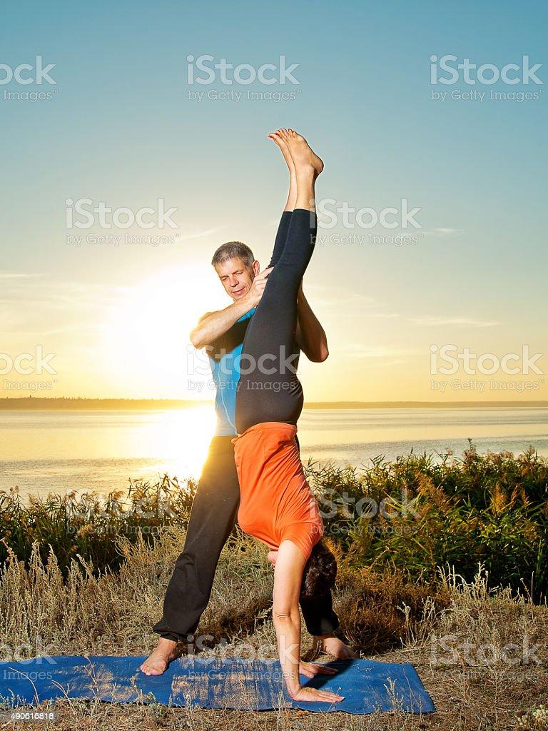smiling couple making yoga exercises outdoors stock photo