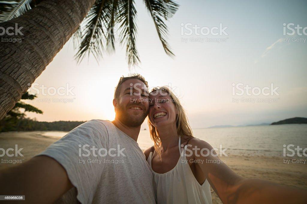 Smiling couple on beach taking selfie stock photo