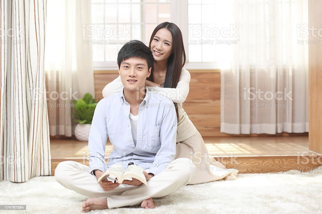 Smiling couple on floor in living-room royalty-free stock photo