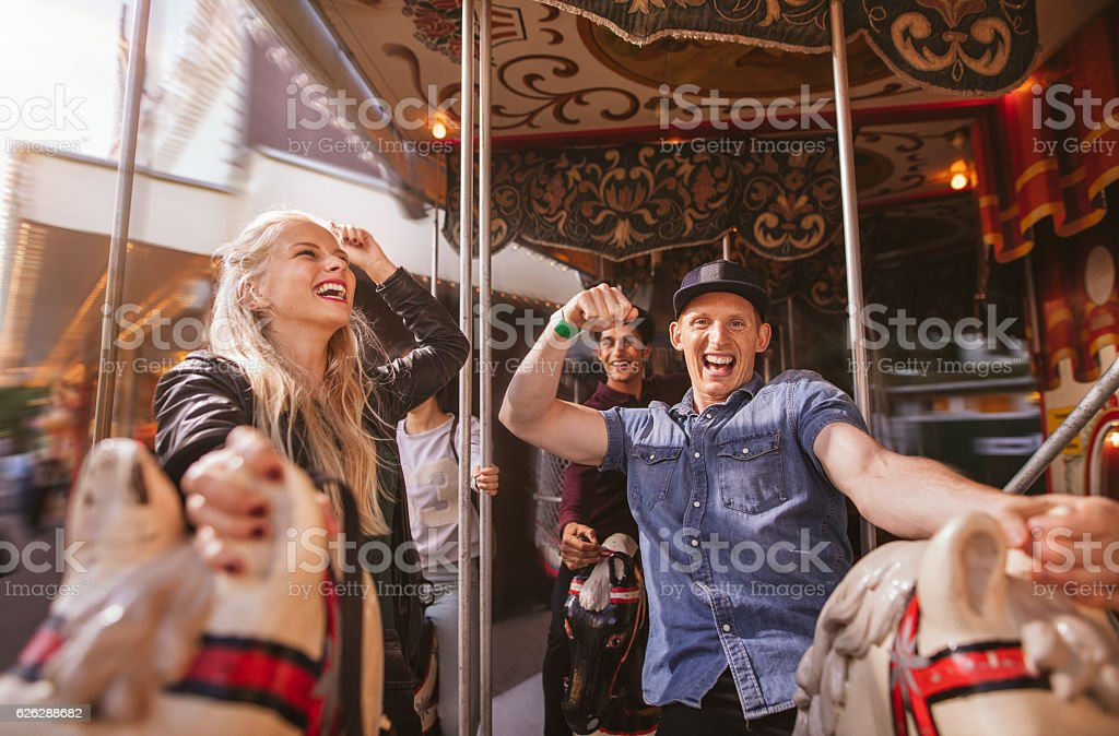 Smiling couple on horse carousel ride at fairground stock photo