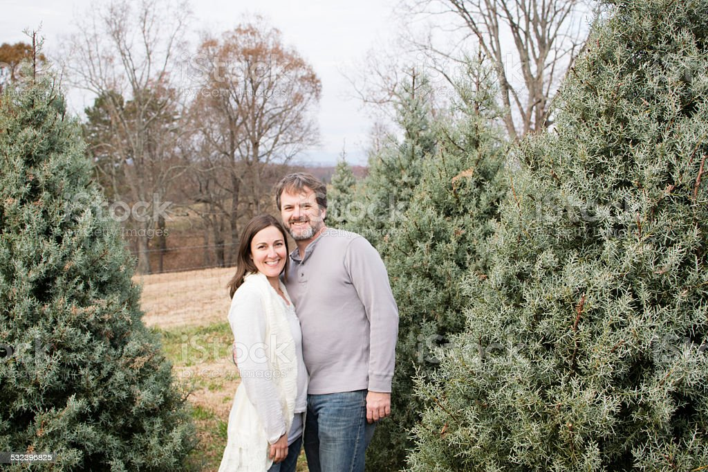 Smiling Couple poses at a Christmas Tree Farm stock photo