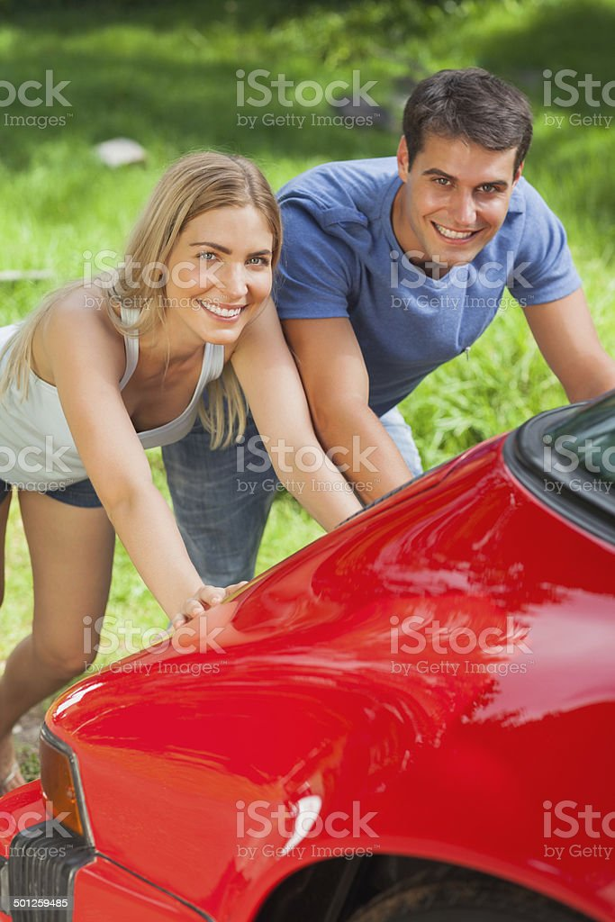 Smiling couple pushing their broken down car stock photo