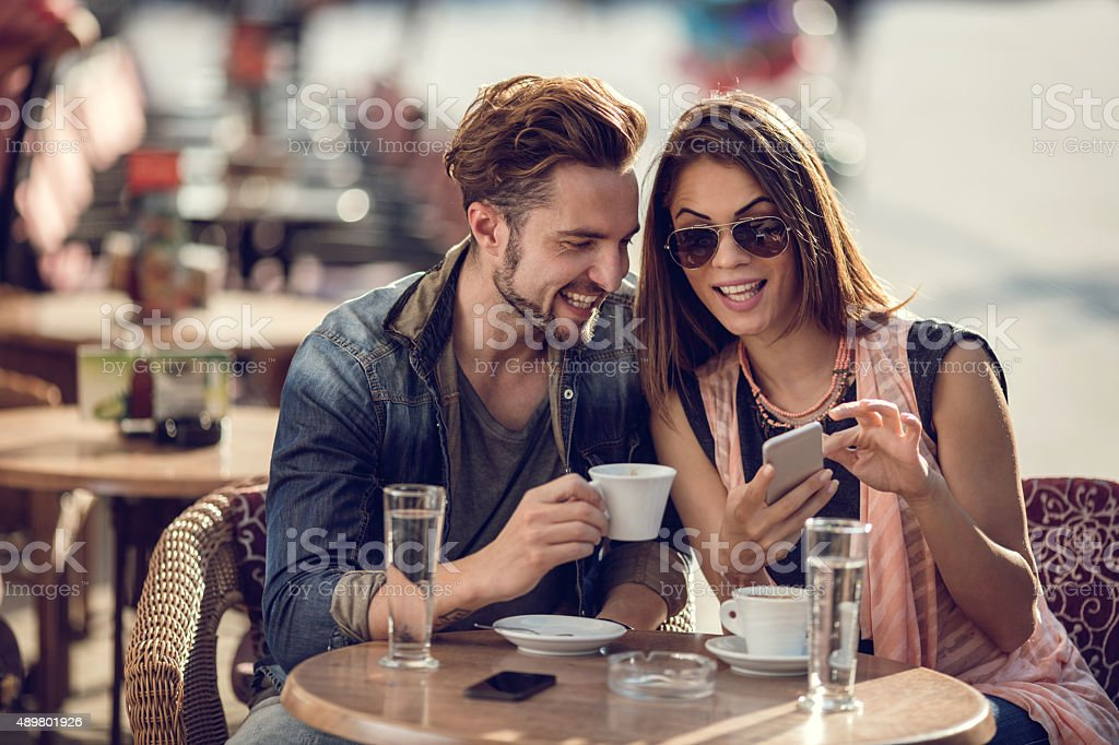 Smiling couple relaxing in a cafe and using smart phone. stock photo
