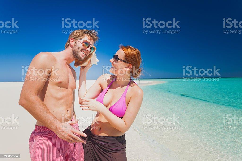 smiling couple sea shell calling tropical island beach stock photo