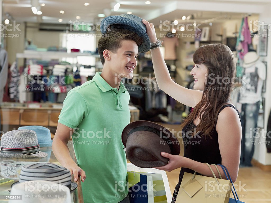 Smiling couple shopping for hats in store royalty-free stock photo