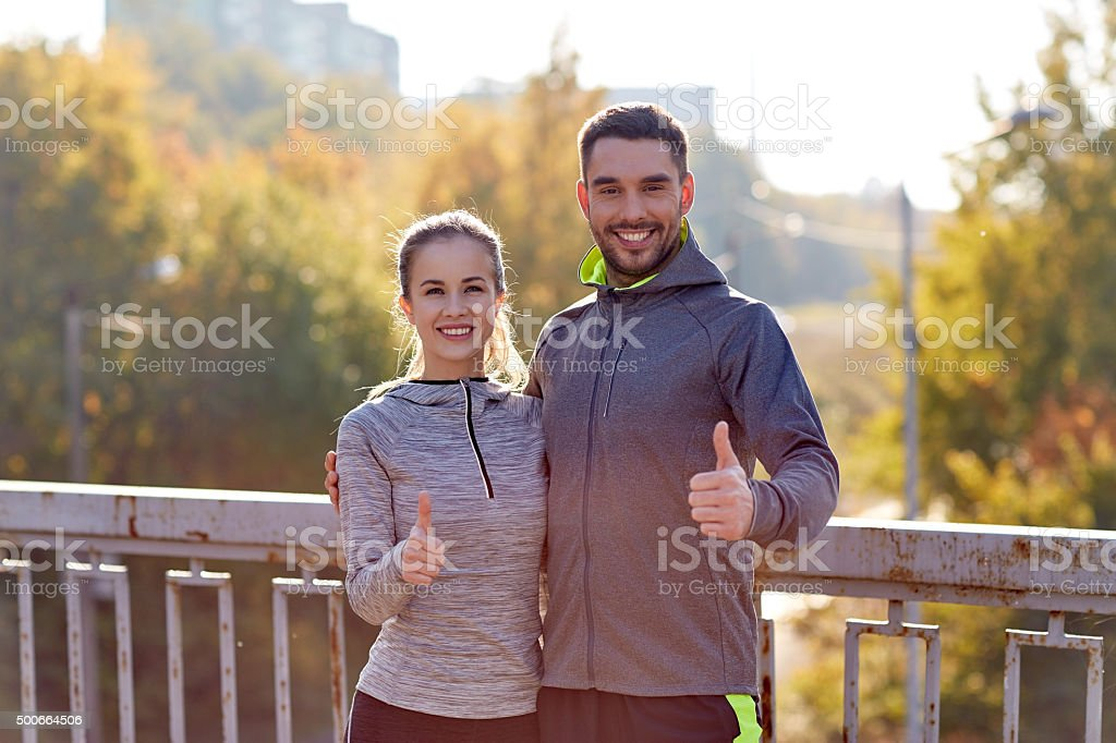 smiling couple showing thumbs up outdoors stock photo