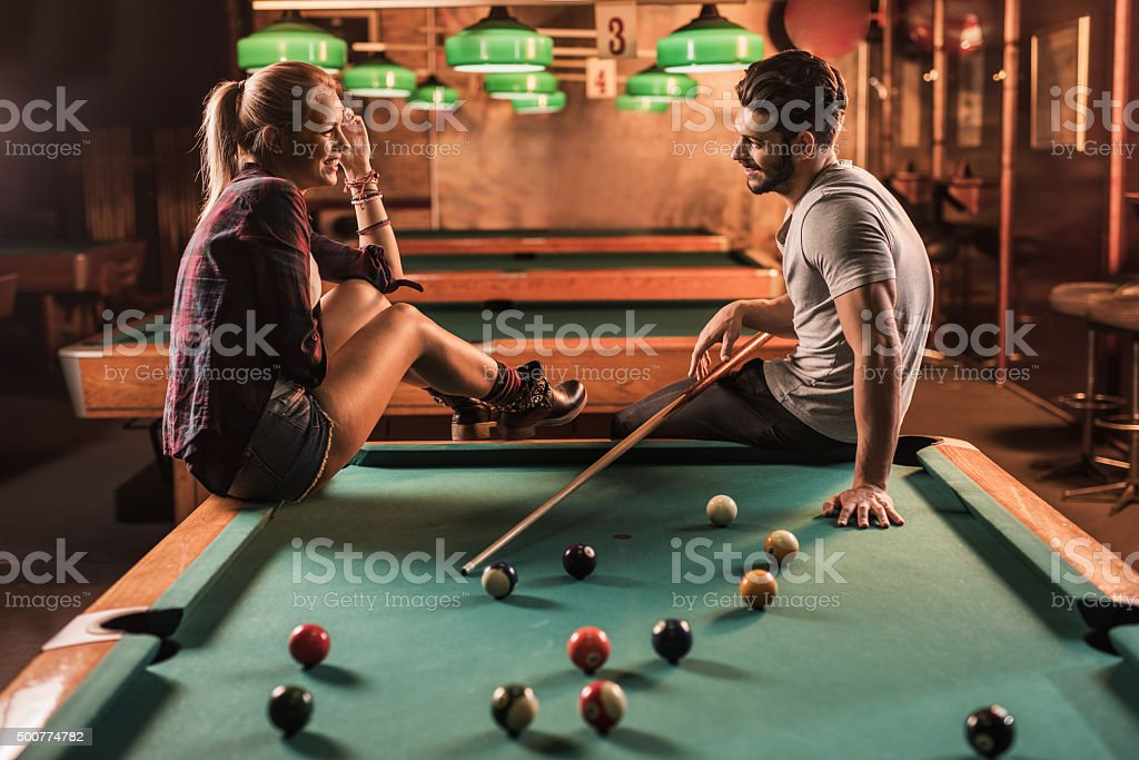Happy couple flirting while playing billiard in a pub.