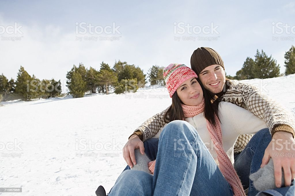 Smiling couple sitting on the snow stock photo