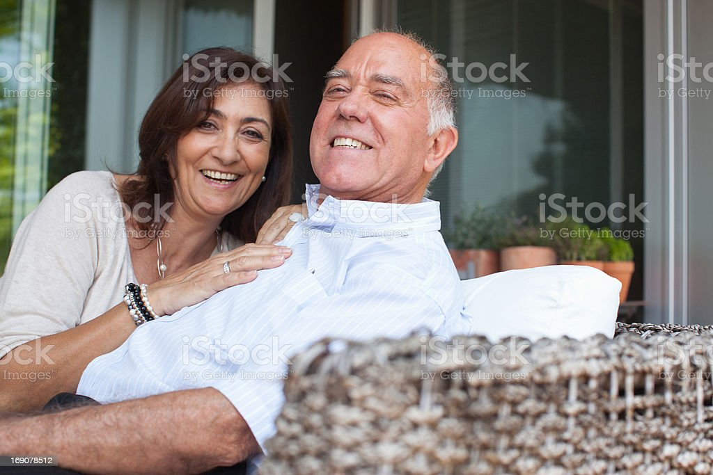 Smiling couple sitting together outdoors stock photo