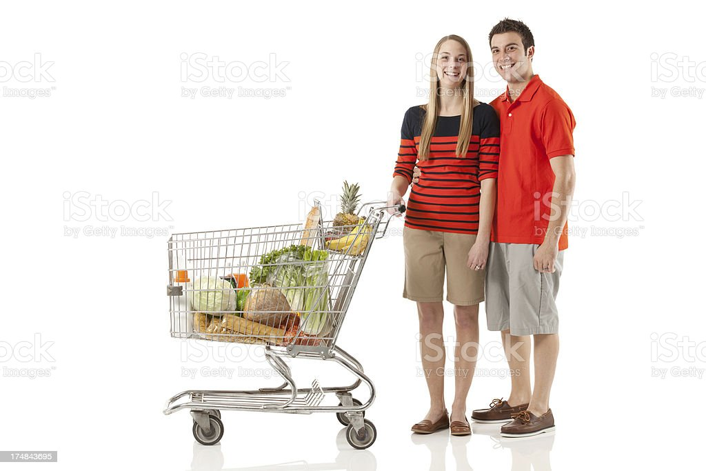 Smiling couple standing near a shopping cart in supermarket royalty-free stock photo