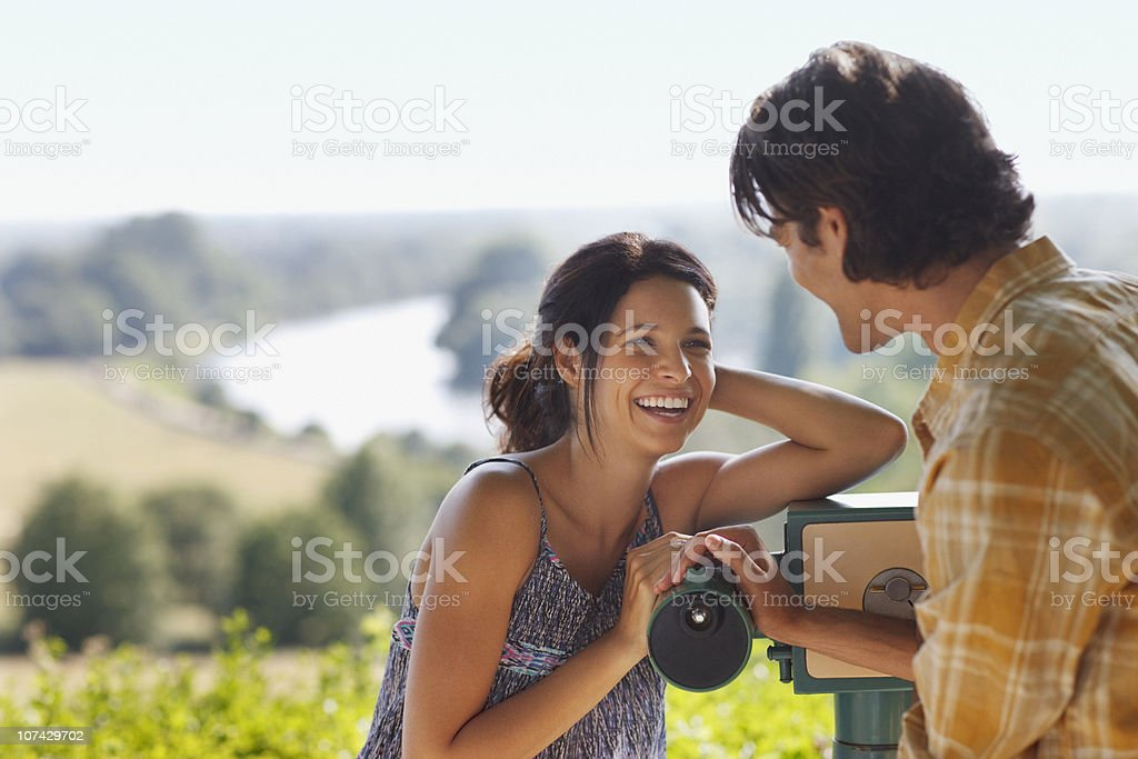 Smiling couple standing near hand-held telescope royalty-free stock photo