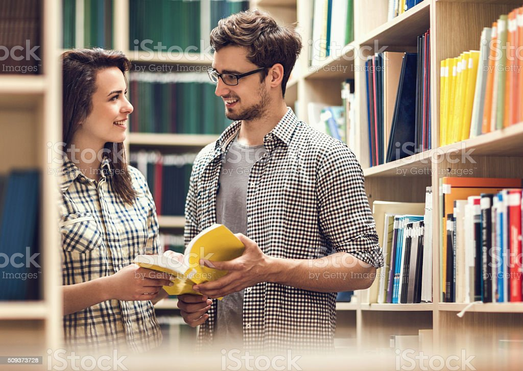 Smiling couple talking to each other in a library. stock photo