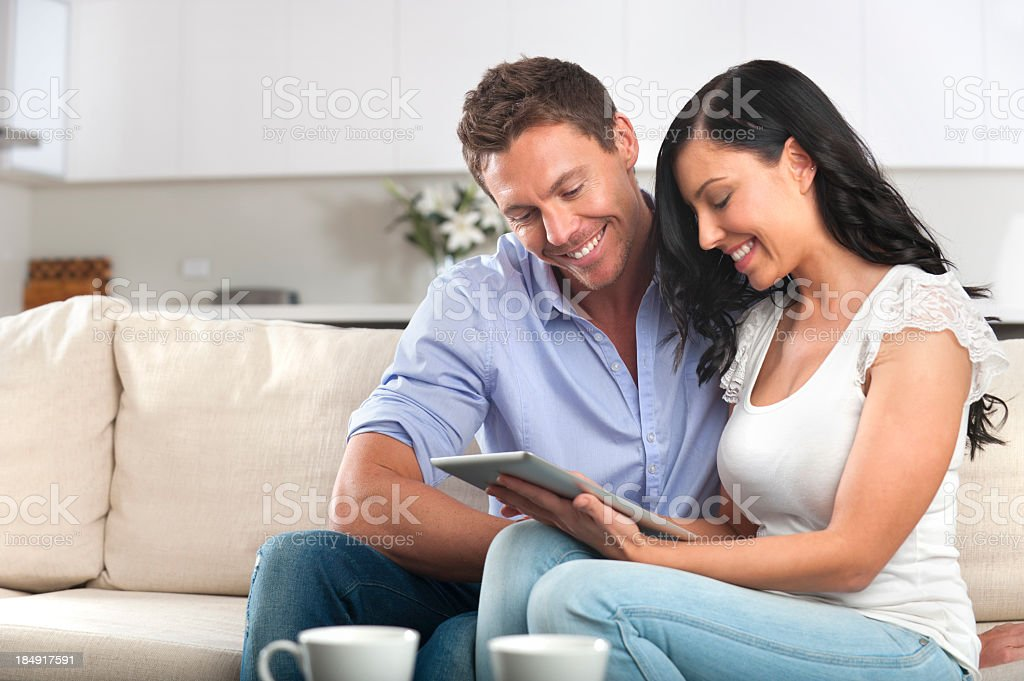 Smiling couple using a digital tablet royalty-free stock photo