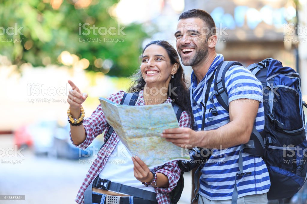 Smiling couple using a map on street stock photo