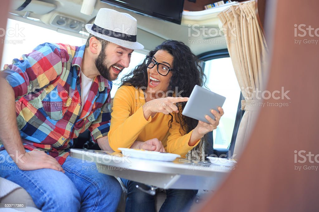 Smiling couple using digital tablet inside of a camper stock photo
