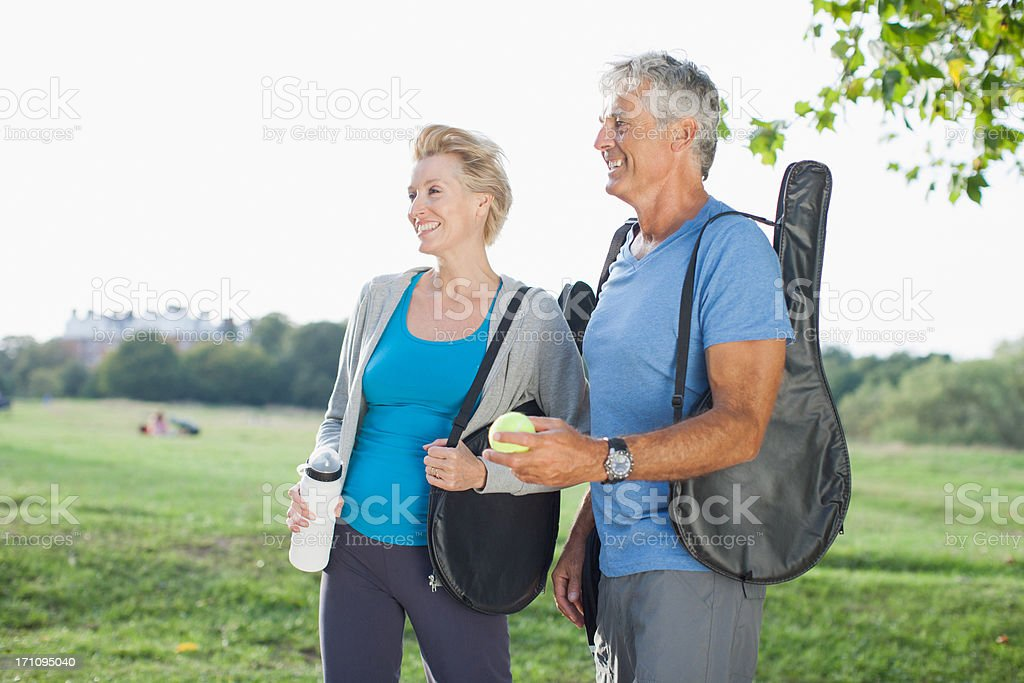 Smiling couple walking with tennis racquets stock photo