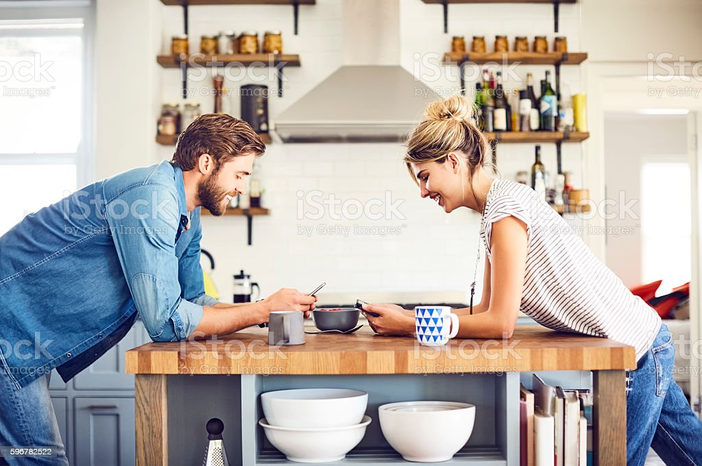 Smiling couple with digital tablets leaning on kitchen island stock photo