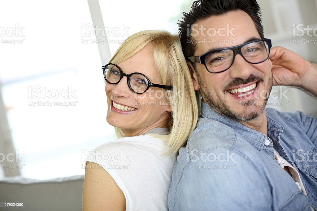 Smiling couple with eyeglasses sitting on couch royalty-free stock photo