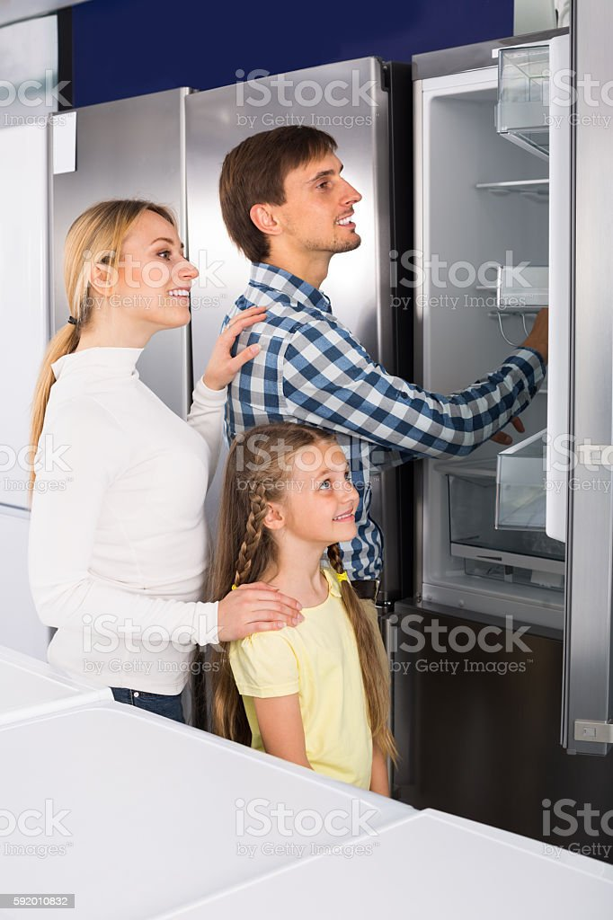 Smiling couple with girl choosing refrigerator stock photo