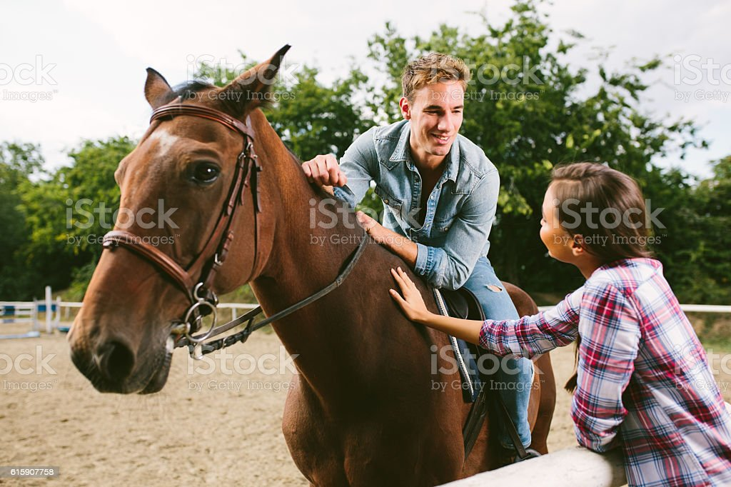 Smiling couple with horse talking to each other. stock photo
