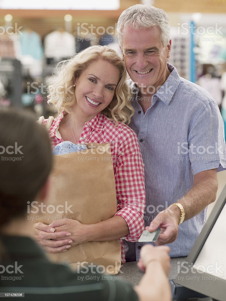 Smiling couple with shopping bag handing credit card to cashier royalty-free stock photo