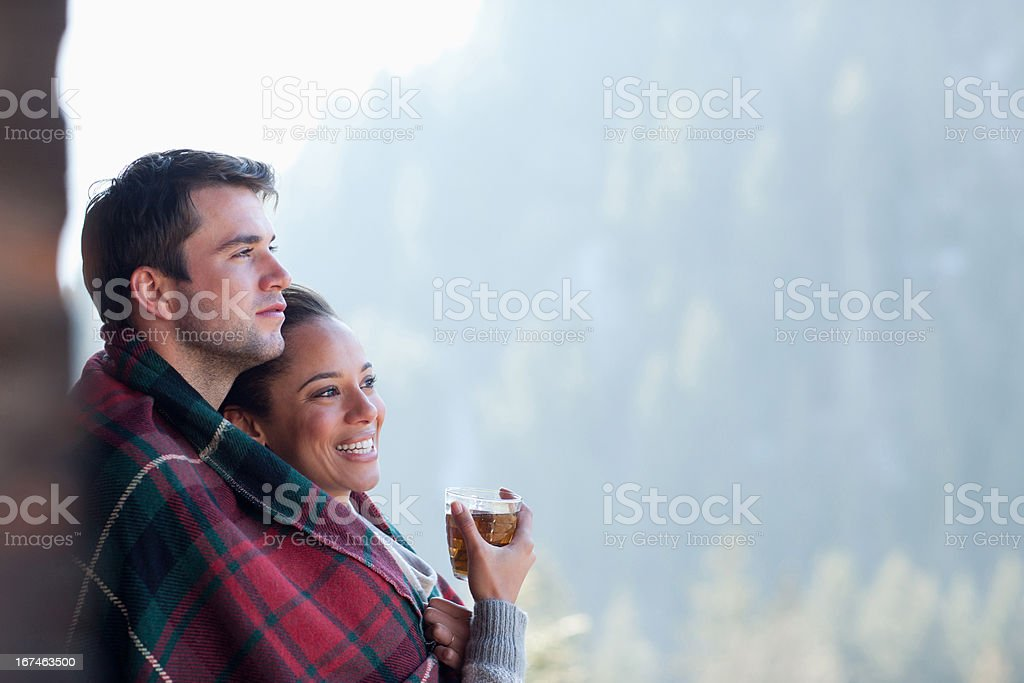 Smiling couple wrapped in a blanket and drinking tea outdoors royalty-free stock photo