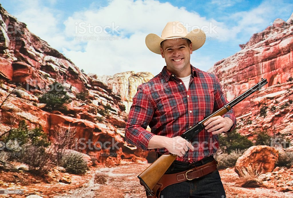 Smiling cowboy holding rifle at mountain stock photo
