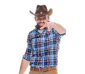 Smiling cowboy pointing at camera
