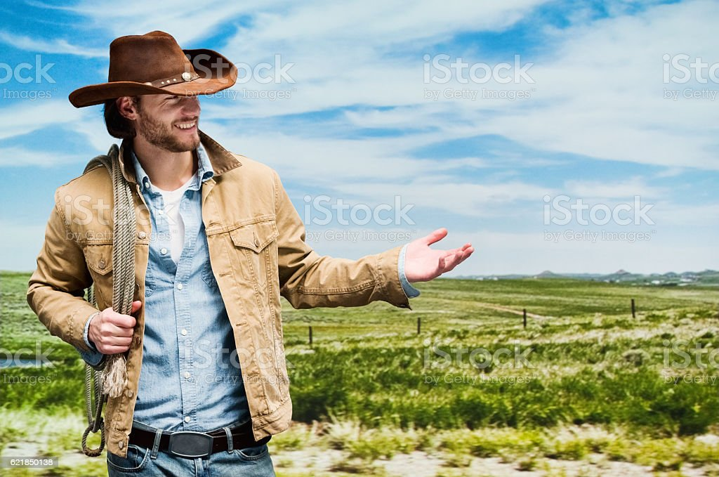 Smiling cowboy presenting outdoors stock photo