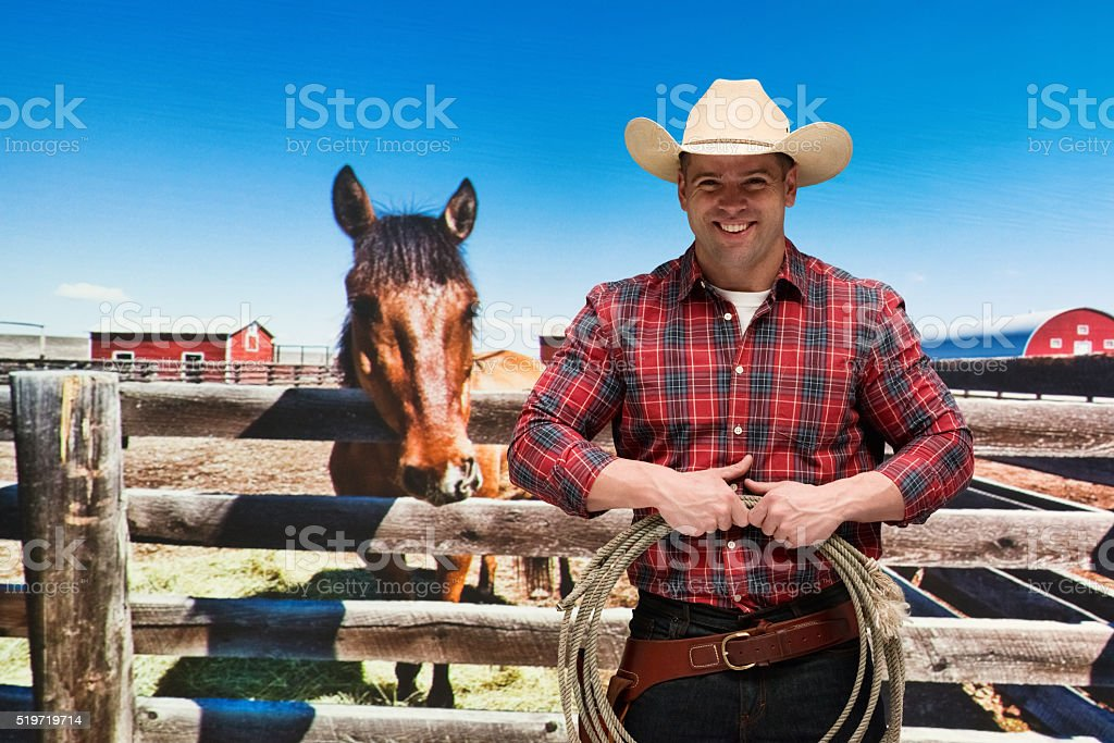 Smiling cowboy standing and holding lasso stock photo