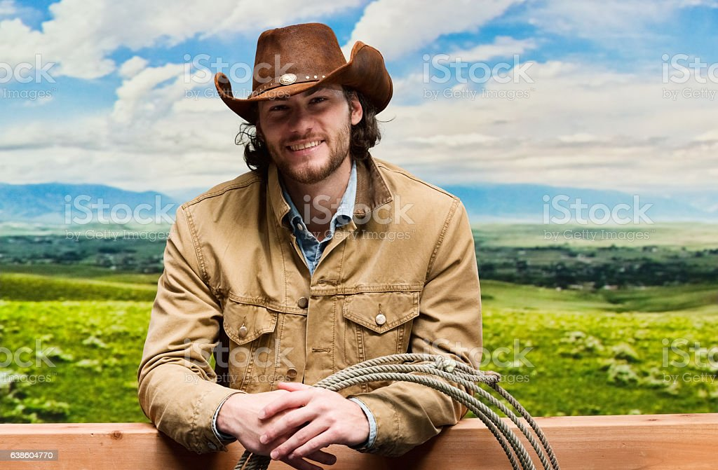 Smiling cowboy standing outdoors stock photo