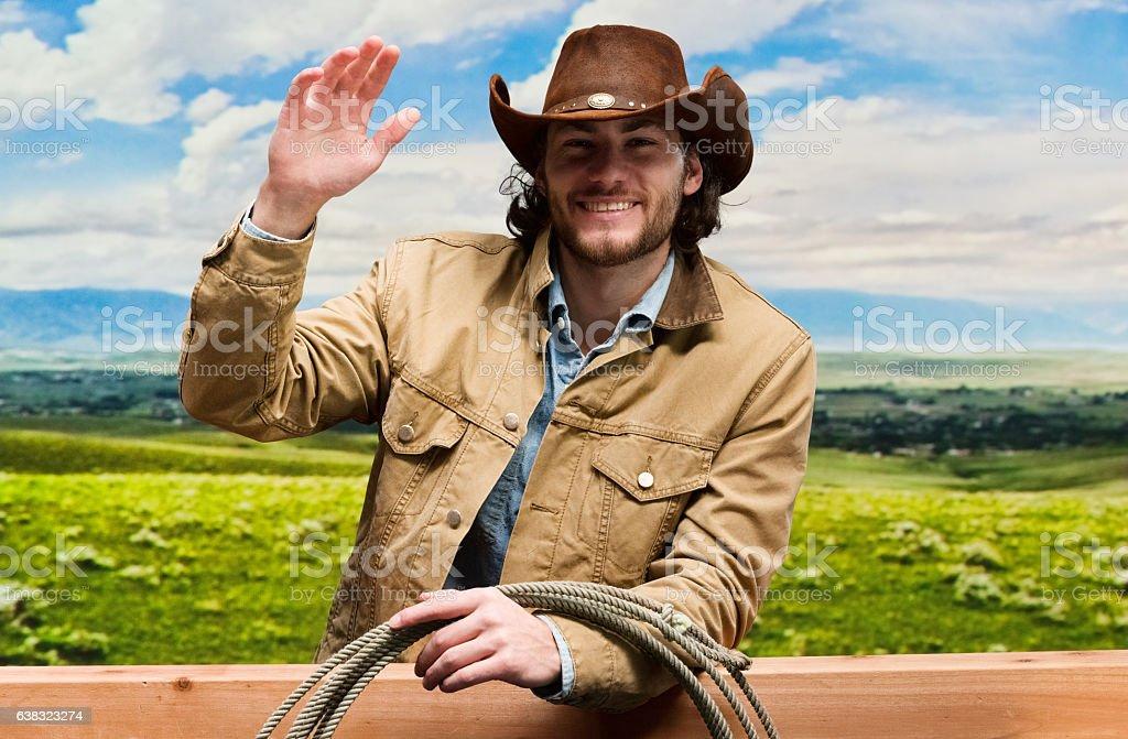 Smiling cowboy waving hand outdoors stock photo