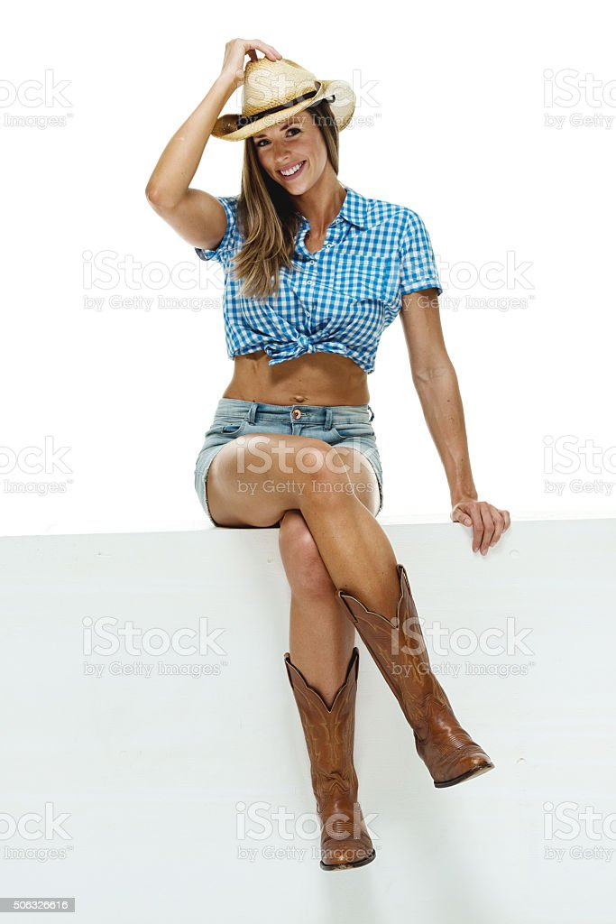 Smiling cowgirl on box and looking at camera stock photo