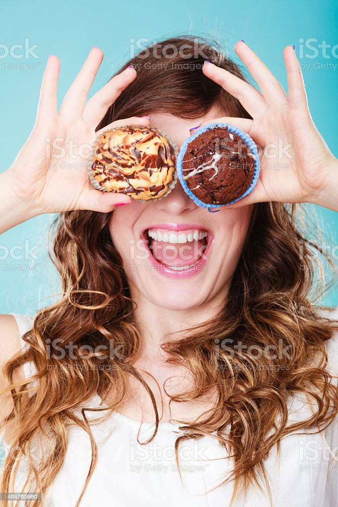 Smiling crazy woman holds cakes in hand stock photo